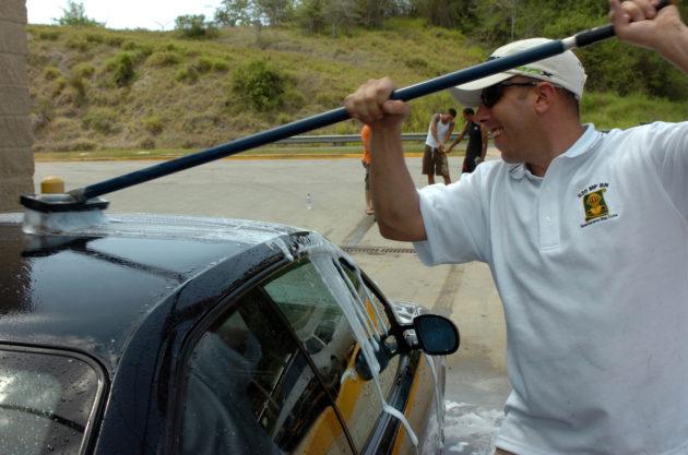 """Army Staff Sgt. Joseph Lobban foam-scrubs a patron's car clean at the Joint Task Forces' Joint Detention Group Ball Carwash fundraiser, May 24, at the car washing station near the Lyceum Theater. The car wash was held as a fundraiser for the JDG Ball in September to help offset the cost for the attending lower enlisted and will """"probably be the first of many,"""" according to SSG Dixie Bivens, whom was there handling money. JTF Guantanamo conducts safe and humane care and custody of detained enemy combatants. The JTF conducts interrogation operations to collect strategic intelligence in support of the Global War on Terror and supports law enforcement and war crimes investigations. JTF Guantanamo is committed to the safety and security of American service members and civilians working inside its detention facilities."""
